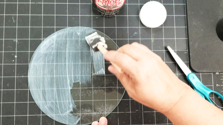 Adding Mod Podge to the under side of the glass cutting board.