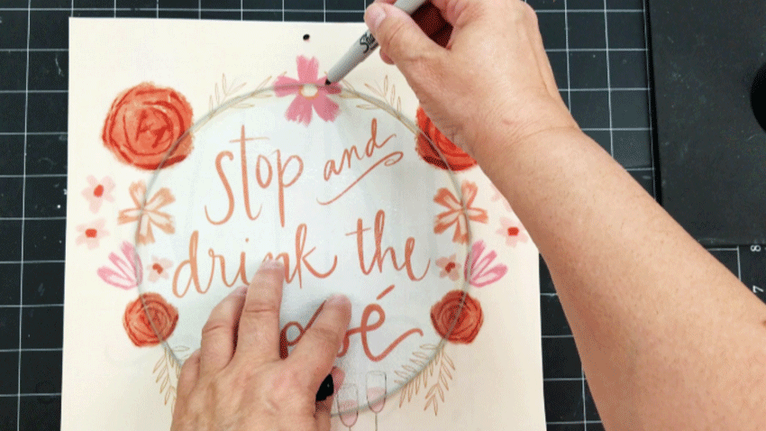 Tracing the glass cutting board onto the calendar page with a sharpie.