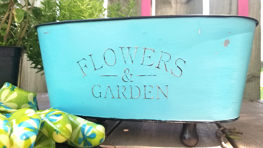 Close up photo of the finished metal flower container with a distressed chalk paint finish.