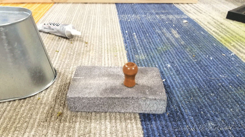 Sanding the little wood feet before adhering them to the bottom of the metal container