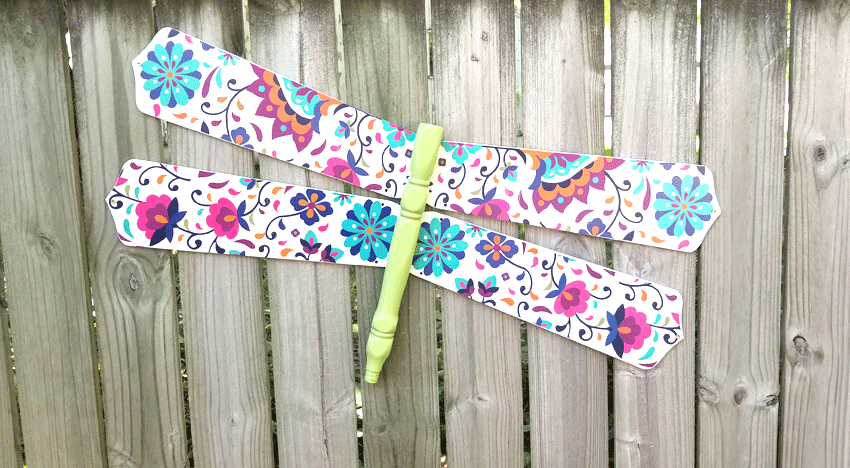 The finished colorful dragonfly DIY wood craft hanging on the fence.