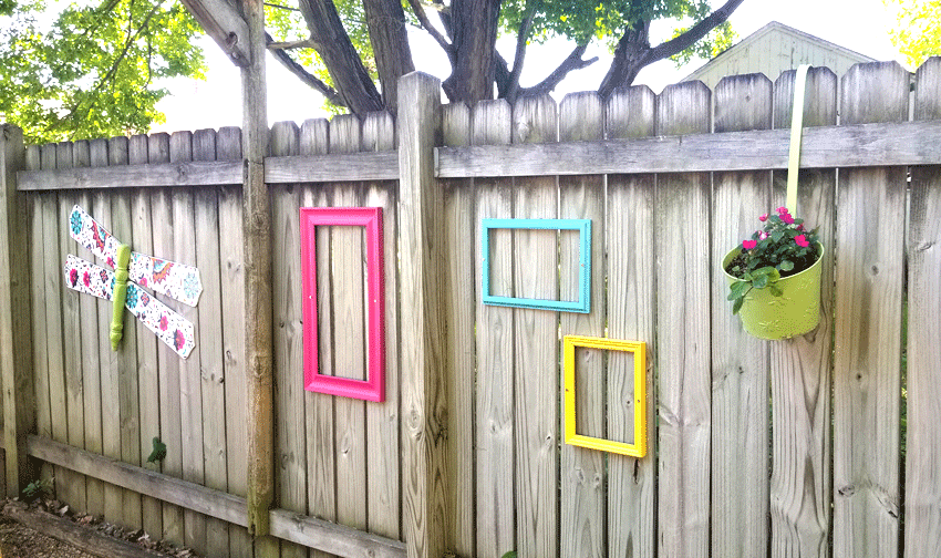 The finished dragonfly DIY Wood Craft hanging on the fence next to the painted frames.