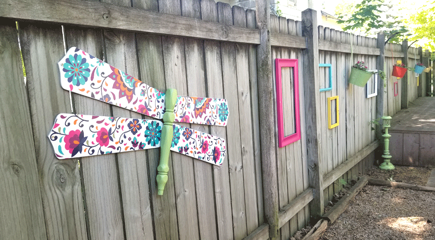 The finished dragonfly hung up on the fence with the colorful frames.