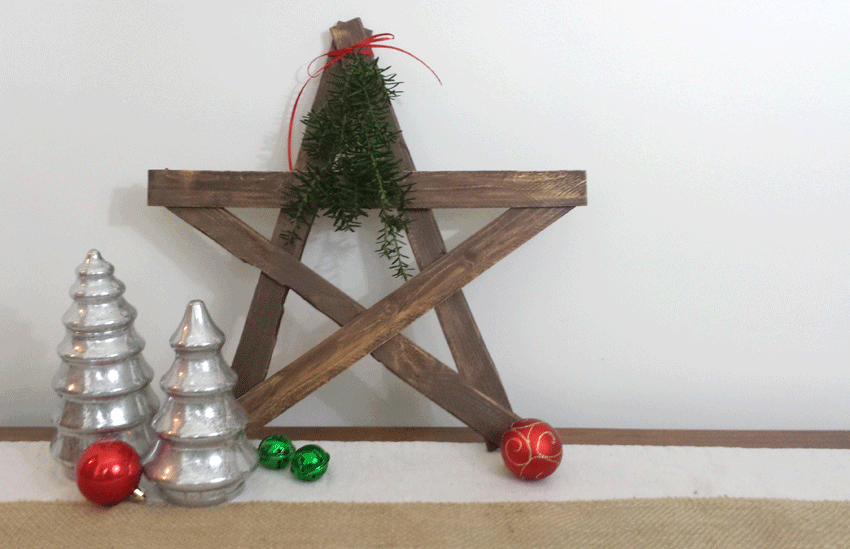 Finished wooden star with ornaments and trees around it.