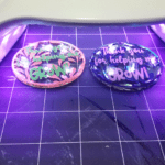 Using the UV light to cure the resin on top of the diy keychains